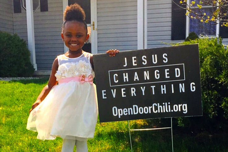 Girl standing next to Jesus Changed Everything sign in yard